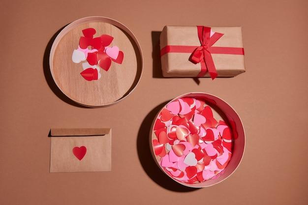 Valentine dag samenstelling. aanwezig of geschenkdoos rode harten. envelop ansichtkaart met confetti