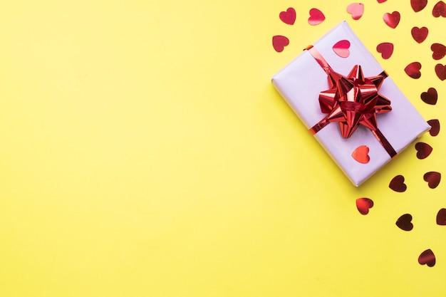 Valentine dag samenstelling, groet geschenkdoos met confetti harten op gele achtergrond. plat leggen.