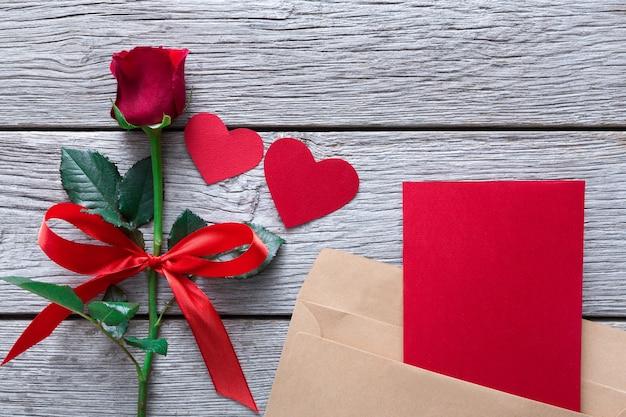 Valentine-dagachtergrond, harten, kaart en roze bloem op hout