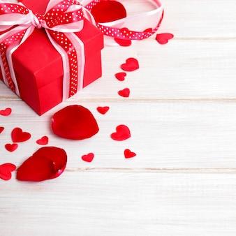 Valentine-dagachtergrond van giftdoos en roze bloemblaadjes op wit hout