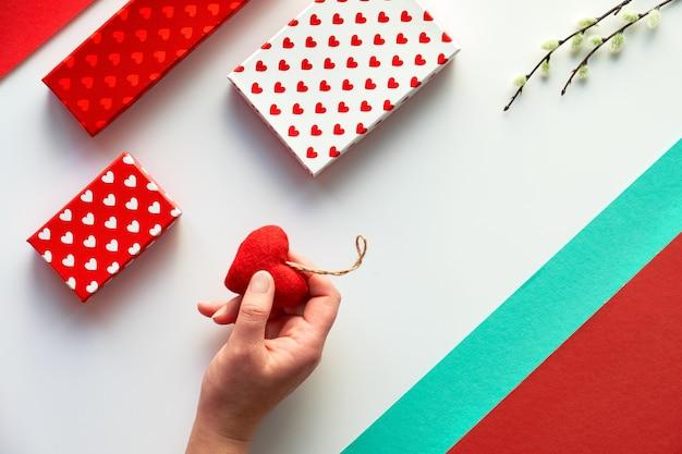 Valentine-dagvlakte lag, hoogste mening op wit. geometrische achtergrond met pussy willow. geschenkdozen en zacht textiel speelgoed hart in de hand. geometrische tweekleurige split papier achtergrond ..