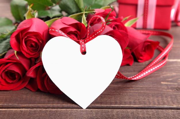 Valentine gift label en rode rozen op een houten bord Gratis Foto