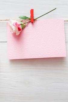 Valentine, lege wenskaart en roze bloem op wasknijper op witte rustieke houten planken