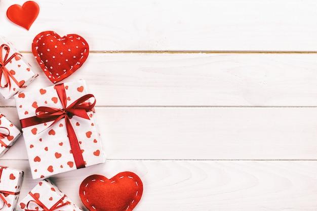 Valentine of andere vakantie handgemaakte cadeau in papier met rode harten en geschenken doos in vakantie wrapper. huidige vak cadeau op houten tafelblad weergave met kopie ruimte, lege ruimte voor ontwerp