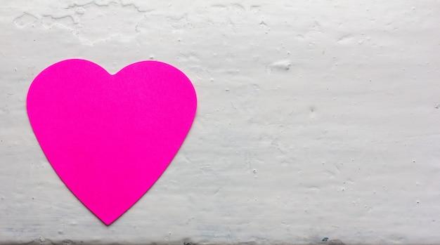 Valentine - papieren hart magenta kleuren tegen het wit geverfde oppervlak