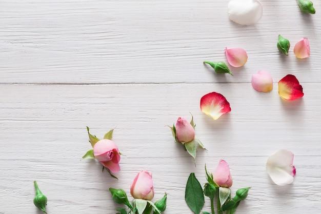 Valentine, roze roze bloemen en bloemblaadjes verspreid over wit rustiek hout, bovenaanzicht met kopie ruimte