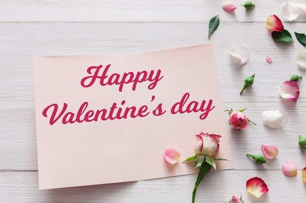 Valentine, roze roze bloemen en bloemblaadjes verspreid over wit rustiek hout en open wenskaart