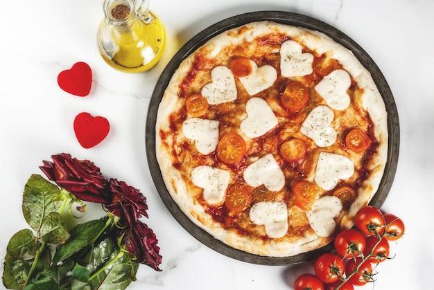 Valentine-vakantievoedsel, pizzamargarita met hartvormige kaas, wit marmer, copyspace hoogste mening, met rozen