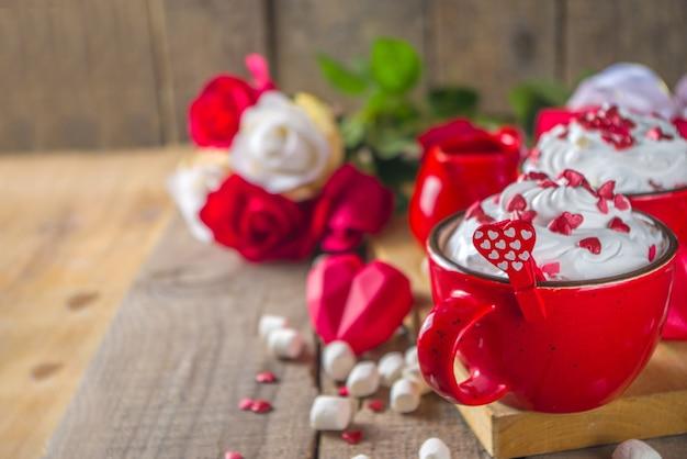 Valentine warme chocolademelk of koffie, twee rode kopjes met warme chocolademelk of latte drinken Premium Foto
