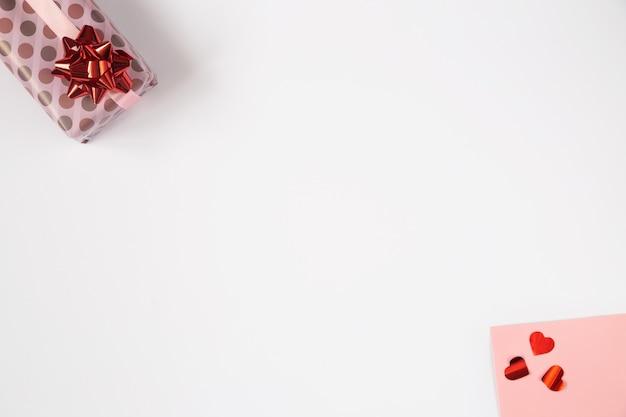 Valentines achtergrond, plat leggen met roze geschenken en rode harten. verjaardag, moederdag, valentijnsdag foto met kopie ruimte op wit.