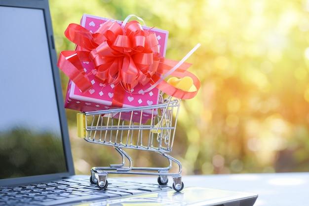Valentines day shopping en gift box roze huidige vak met red ribbon bow op winkelwagen online winkelen