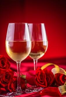 Valentines of bruiloft concept. wijnbekers rode rozen en romantische setting voor twee in rood. wenskaart voor jubileum of jubileum.