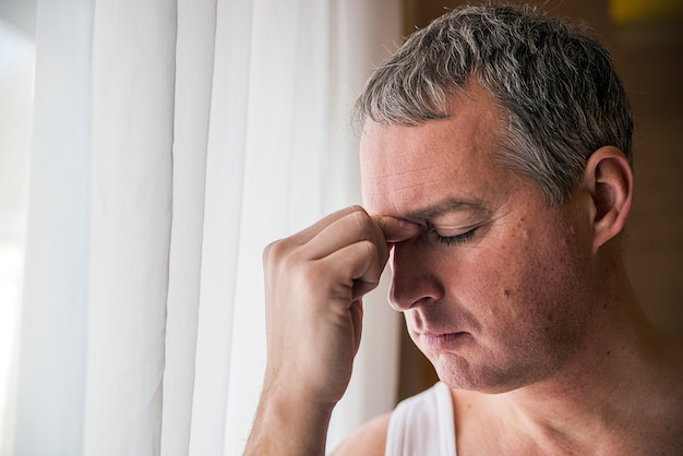 Valiente hombre de mediana edad mirando a la ventana, hombre de negocios triste y deprimido solo. hombre mirando a través de la ventana mirando preocupado, deprimido, pensativo y sufriendo sufrimiento solitario en la presión de trabajo o problemas personales concepto con espacio de copia