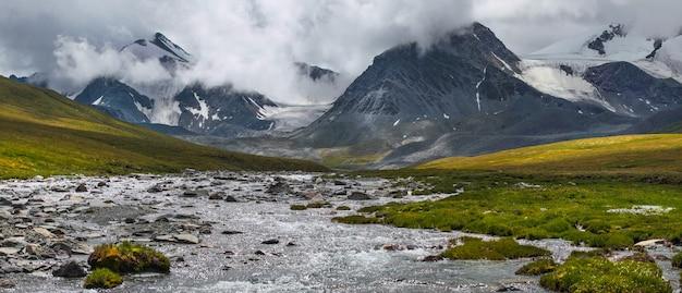 Vallei in de bergen van altai, barre weersomstandigheden. wolken bedekken de top, een wilde rivier