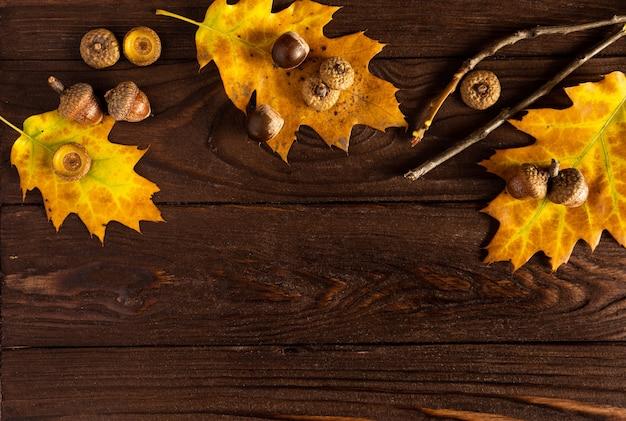 Vallen. gekleurde gevallen bladeren, eikels op een houten bruine achtergrond, lay-out, kopieer ruimte