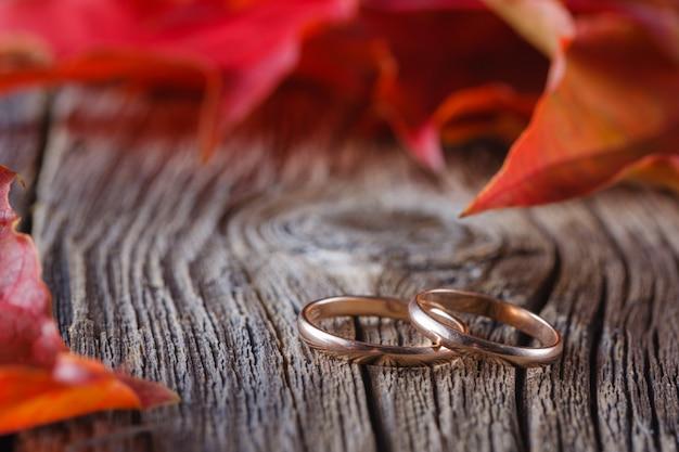 Vallen op bladeren op verweerde tafel met trouwringen