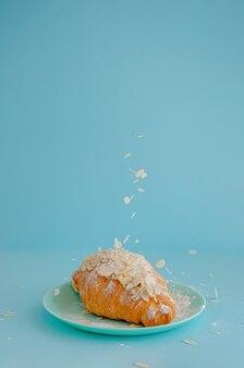 Vallende amandelvlokken op vers gesteunde croissant op blauwe muur. kopieer ruimte, verticaal.