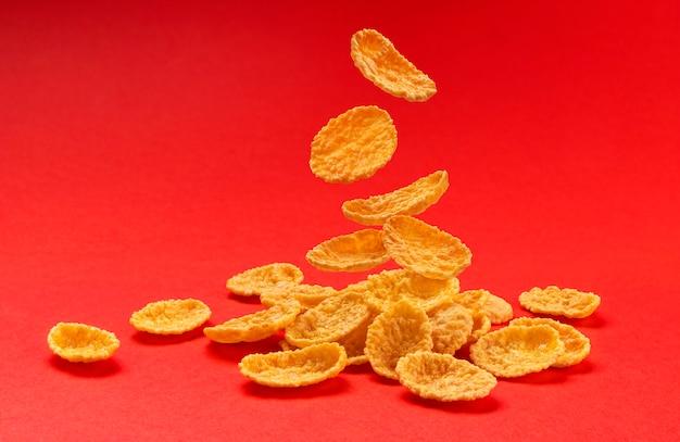 Vallende cornflakes geïsoleerd op rood