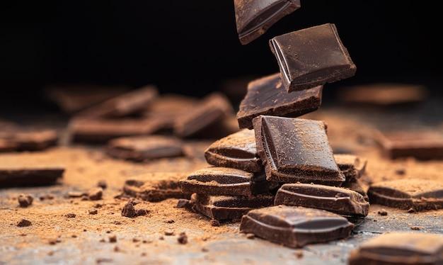Vallende gebroken chocoladerepen op zwarte achtergrond