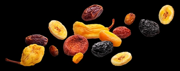 Vallende gedroogde vruchten geïsoleerd op zwarte achtergrond