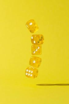 Vallende gele dobbelstenen op gele achtergrond Gratis Foto