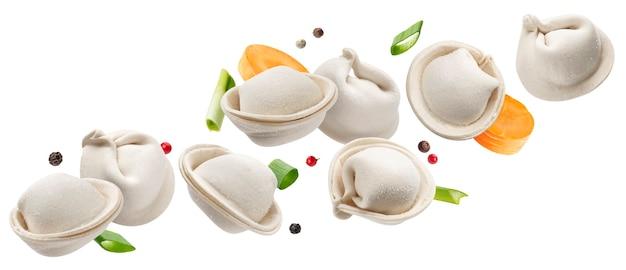 Vallende rauwe dumplings, bevroren zelfgemaakte russische pelmeni geïsoleerd op wit