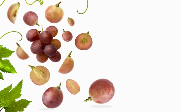 Vallende rode druif met bladeren geïsoleerd op een witte achtergrond selectieve focus