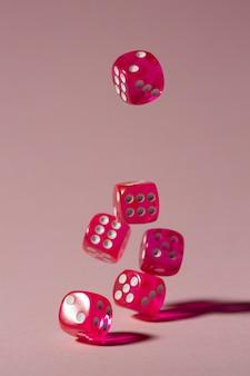 Vallende roze dobbelstenen op roze achtergrond