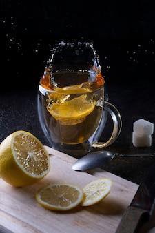Vallende schijfjes citroenen in een mok met hete thee op zwarte achtergrond, thee spatten in verschillende richtingen.