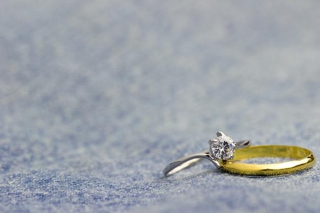 Valse diamanten ring en gouden ring geplaatst op jean jecket