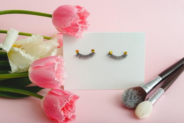 Valse wimpers make-up borstels en bloemensamenstelling op roze achtergrond.