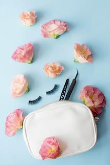 Valse wimpers, zwart pincet en roze bloemen op blauw.