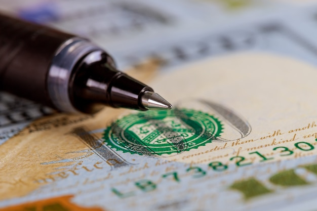 Valuta amerikaanse dollar bankbiljetten close-up met balpen op dollar biljetten