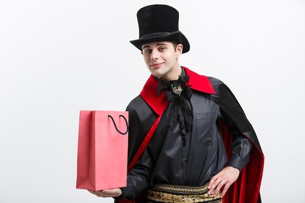 Vampire halloween concept - gelukkige knappe kaukasische vampier die kleurrijke boodschappentas op witte muur houdt.