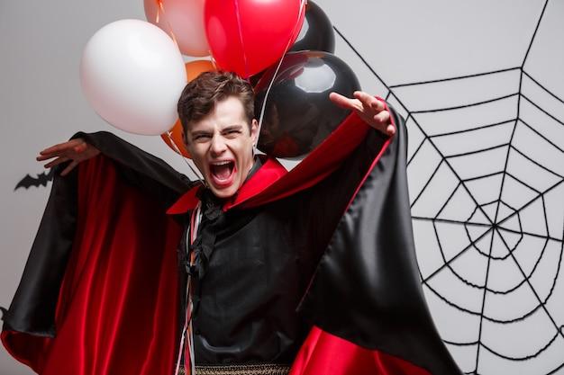 Vampire halloween concept - portret van knappe blanke in vampire halloween kostuum met kleurrijke ballon.