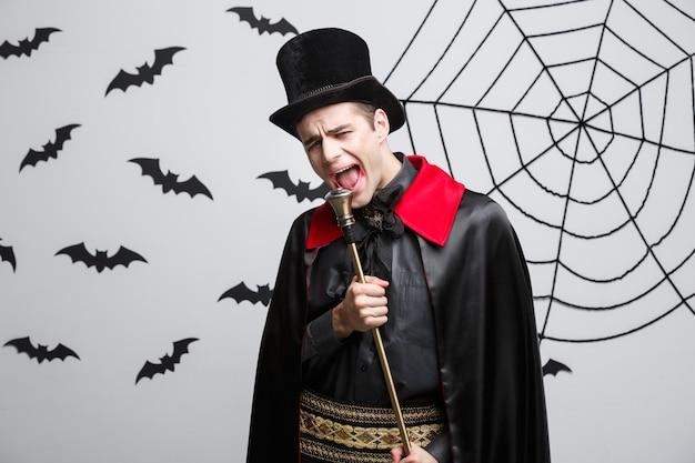 Vampire halloween concept - portret van knappe blanke vampire in zwart en rood halloween kostuum zingen met personeel.