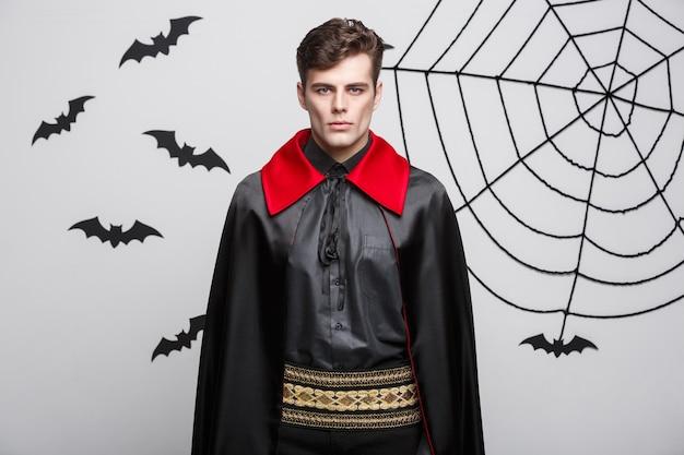 Vampire halloween concept - portret van knappe blanke vampire in zwart en rood halloween-kostuum.