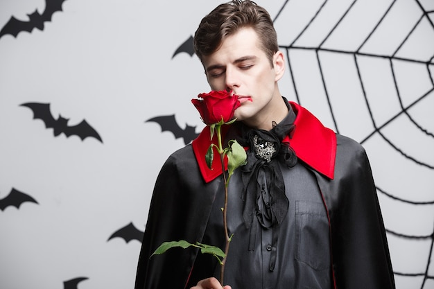 Vampire halloween concept - portret van knappe blanke vampire met mooie rode roos.