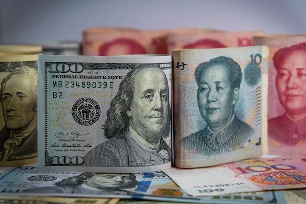 Van aangezicht tot aangezicht van dollar en yuan bankbiljetten die de vs en china oorlogshandel hebben en toenemen