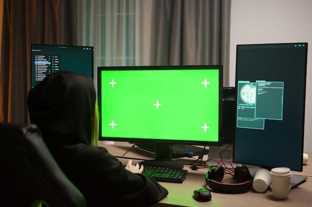 Van achteren geschoten van vrouwelijke hacker die een virus schrijft op computer met groen scherm.
