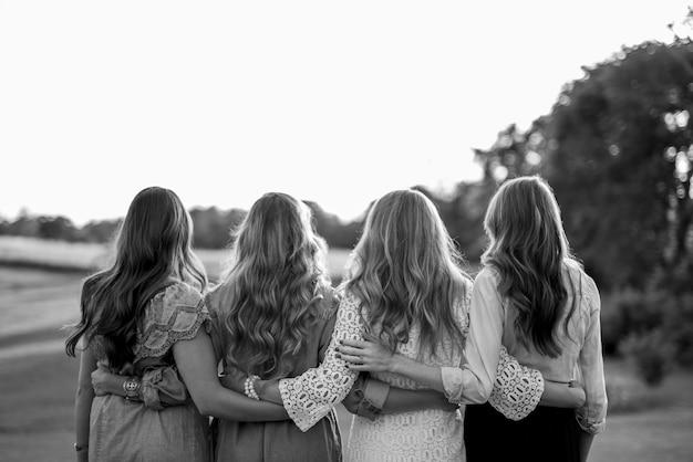 Van achteren neergeschoten van vier vrouwen met hun armen om elkaar heen in zwart-wit