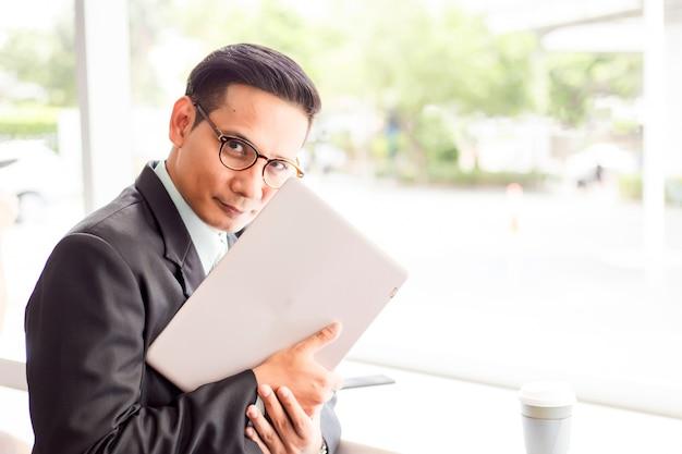 Van bedrijfs azië mens die met laptop werken terwijl het zitten van koffiewinkel