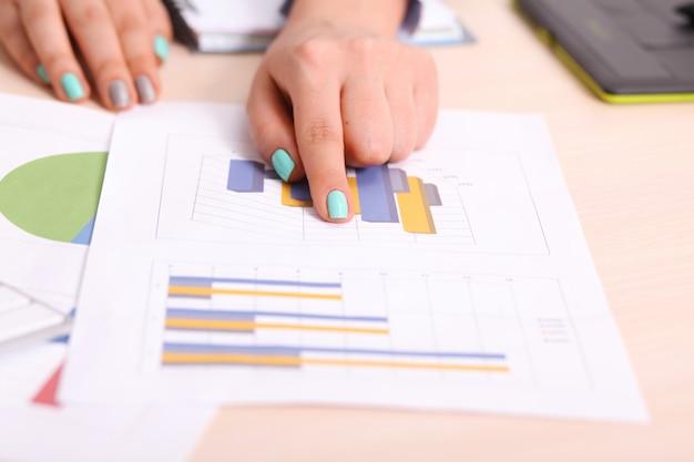 Van bedrijfs azië vrouw die investeringsgrafieken op bureau analyseert