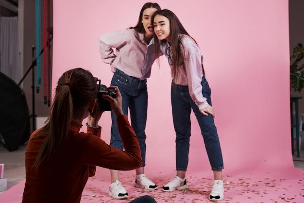 Van beneden. foto van twee meisjes die gefotografeerd door vrouwelijke cameraman in de studio