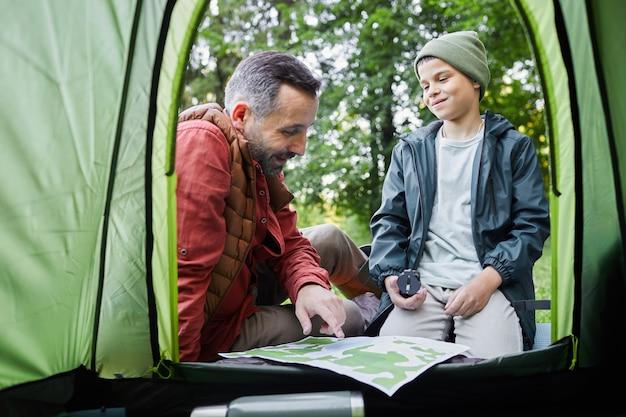Van binnen schot van volwassen vader en zoon zitten door tent tijdens kampeertrip in bos, kopieer ruimte