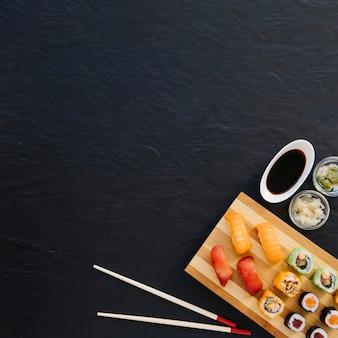 Van boven de eetstokjes en kruiden in de buurt van sushi