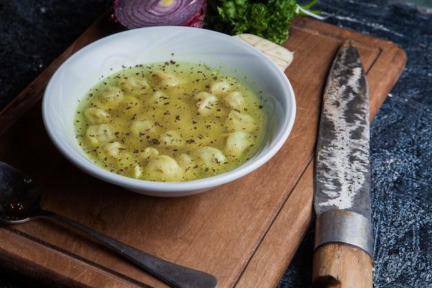 Van boven dushpara met mes en lepel en ui in food board