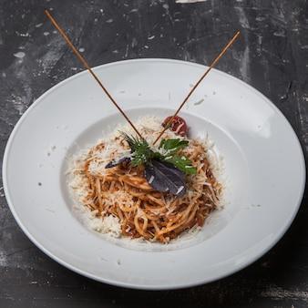 Van boven spaghetti met tomaat en groenten en ricotta kaas in ronde witte plaat