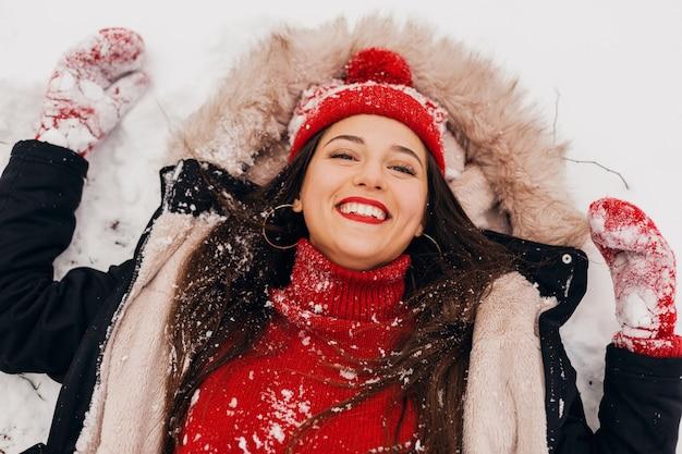 Van bovenaf bekijken op jonge mooie openhartige lachende gelukkige vrouw in rode wanten en gebreide muts dragen zwarte jas liggend in de sneeuw in park, warme kleren, plezier