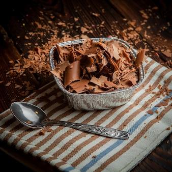 Van bovenaf chocoladeschijfjes met lepel en doek in foliehouder
